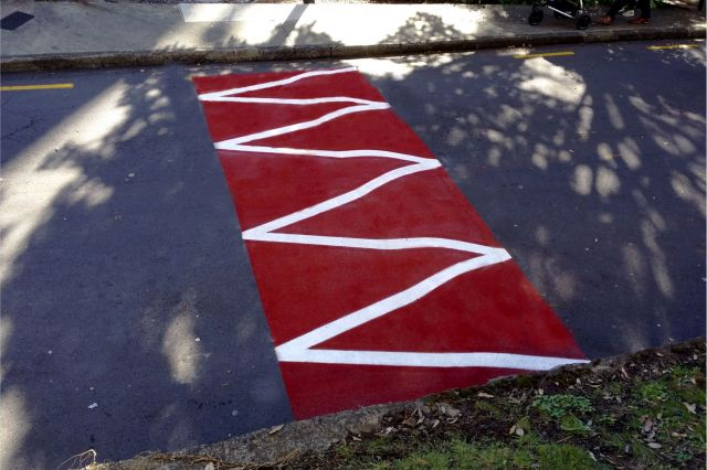 Speed hump renovated with resin and aggregate and marked with tiger teeth stripes